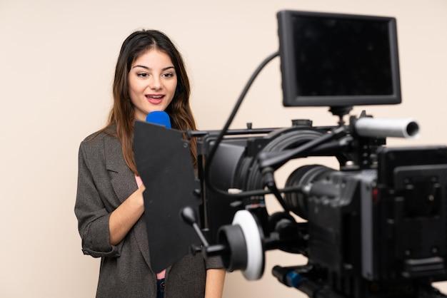Женщина репортера держа микрофон и сообщая новости над изолированной белой стеной Premium Фотографии