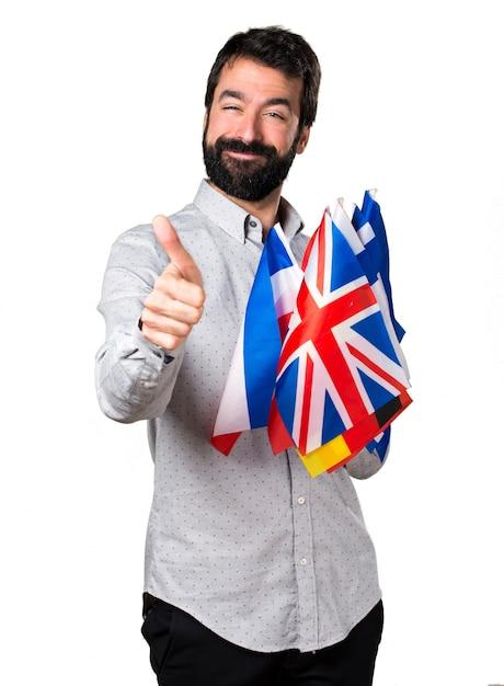 たくさんの旗を持ち、親指で上品な男 無料写真