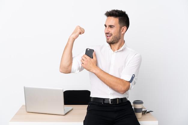 Молодой бизнесмен с мобильным телефоном на рабочем месте, делая сильный жест Premium Фотографии