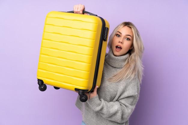 旅行スーツケースと休暇で孤立した紫色の壁の上のティーンエイジャーの女性 Premium写真