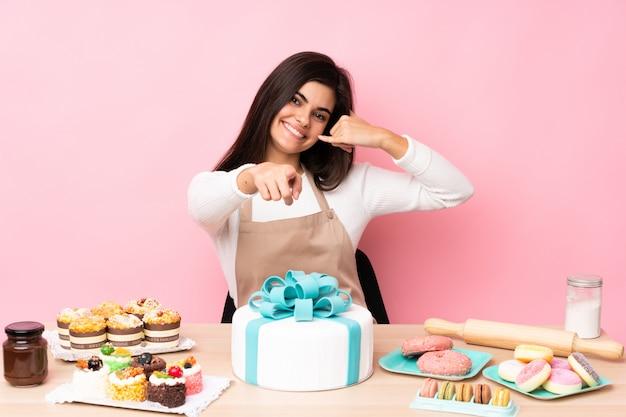 電話のジェスチャーを作るとフロントを指す分離のピンクの壁の上のテーブルに大きなケーキとパティシエ Premium写真