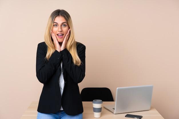 Молодая бизнес-леди в офисе с выражением лица сюрприза Premium Фотографии