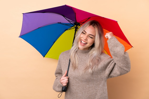 勝利を祝って壁に傘を保持しているティーンエイジャーの女の子 Premium写真