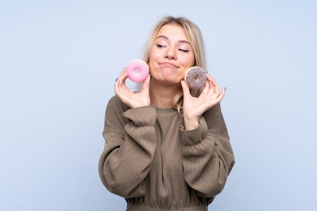 ドーナツを保持している分離の青い壁の上の若いブロンドの女性 Premium写真