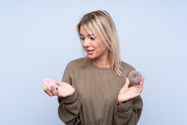 幸せな表情でドーナツを保持している分離の青い壁の上の若いブロンドの女性 Premium写真