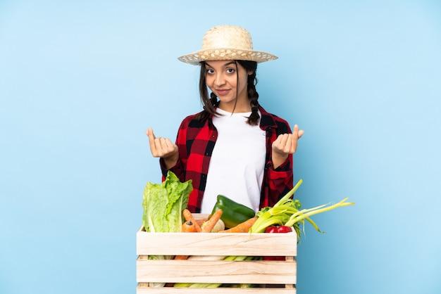 お金のジェスチャーを作る木製のバスケットで新鮮な野菜を保持している若い農家の女性 Premium写真