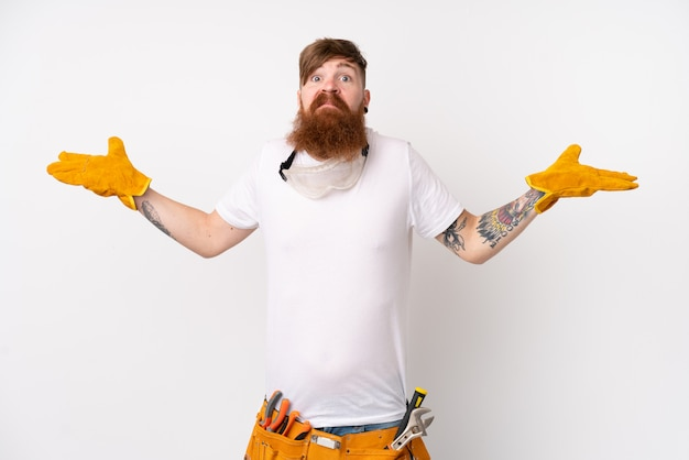 混乱した表情で疑問を持つ孤立した白い壁の上の長いひげを持つ赤毛電気技師男 Premium写真