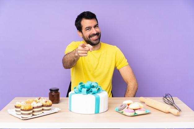 お菓子でいっぱいのテーブルを持つペストリー男 Premium写真