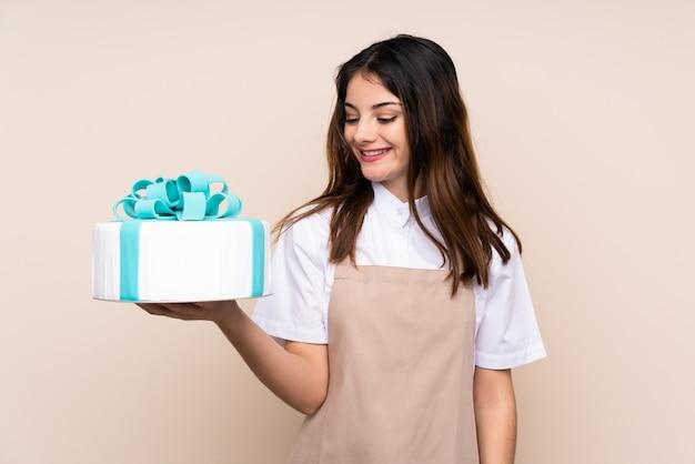Кондитер женщина, держащая большой торт над стеной с счастливым выражением Premium Фотографии