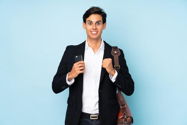勝利を祝っている青い壁の上のビジネスマン Premium写真