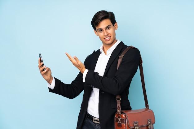 Бизнесмен над синей стеной, протягивая руки в сторону за приглашение прийти Premium Фотографии