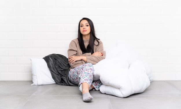 動揺を感じて屋内でパジャマで若いコロンビアの女の子 Premium写真
