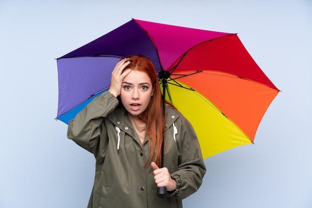 驚きの表情と青で傘を保持している赤毛のティーンエイジャーの女の子 Premium写真
