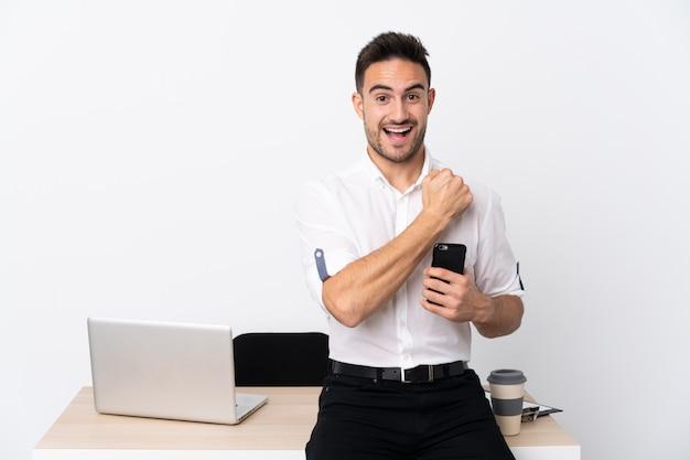 Молодой деловой человек с мобильным телефоном на рабочем месте, празднует победу Premium Фотографии