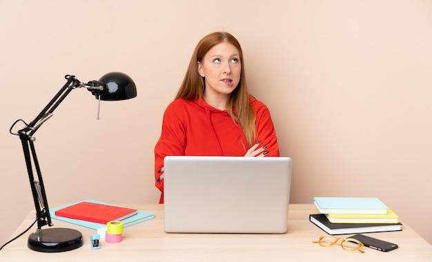 Молодой студент женщина на рабочем месте с ноутбуком с выражением лица путать Premium Фотографии
