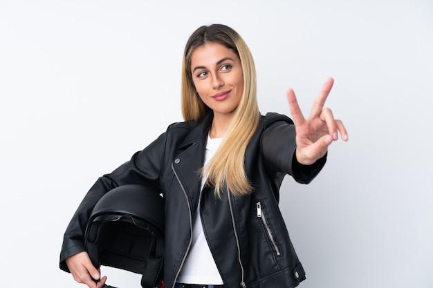 笑みを浮かべて、勝利のサインを示す分離の白い壁の上のオートバイのヘルメットを持つ若いウルグアイ女性 Premium写真