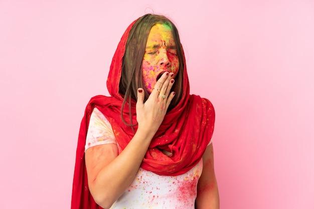 Молодая индийская женщина с красочными порошками холи на лице, изолированные на розовой стене зевая и прикрывая широко открытый рот рукой Premium Фотографии