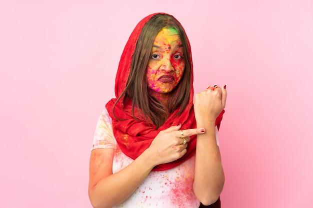 Молодая индийская женщина с красочными порошками холи на лице, изолированные на розовой стене, делая жест опоздания Premium Фотографии