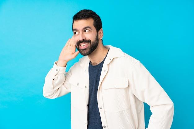 Молодой красавец с белой вельветовой куртке над синей стеной, слушая что-то, положив руку на ухо Premium Фотографии