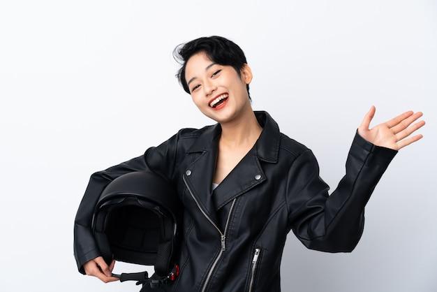 Молодая азиатская девушка с шлемом мотоцикла над изолированной белой стеной салютуя с рукой с счастливым выражением Premium Фотографии