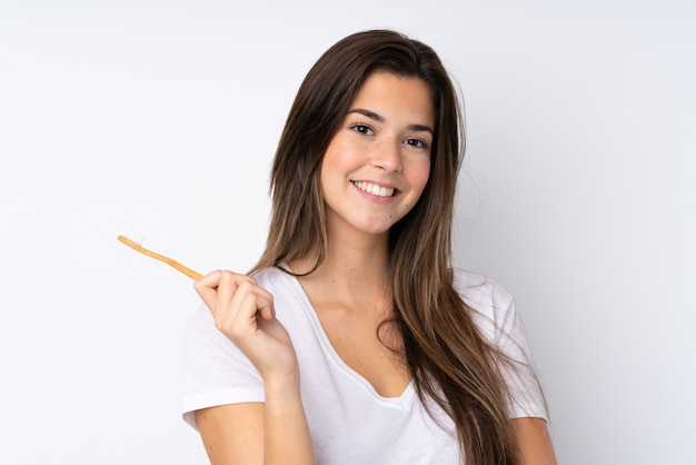 歯ブラシで孤立した壁の上のティーンエイジャーの女の子 Premium写真