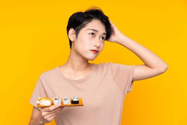 疑いを持つ寿司と混乱の表情を持つ若いアジア女性 Premium写真