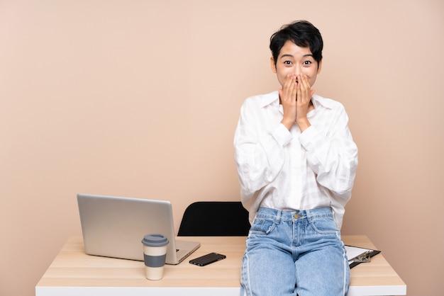 Женщина молодого дела азиатская в ее рабочем месте с выражением лица сюрприза Premium Фотографии