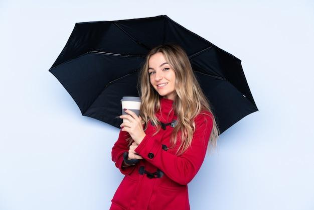Молодая женщина с зимним пальто держит зонтик и кофе на вынос Premium Фотографии