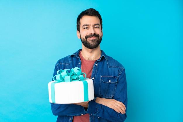 腕を維持する大きなケーキと若いハンサムな男が正面の位置で交差 Premium写真