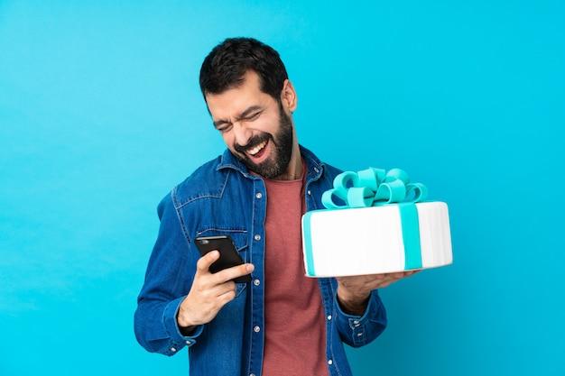 勝利位置に電話で大きなケーキを持つ若いハンサムな男 Premium写真