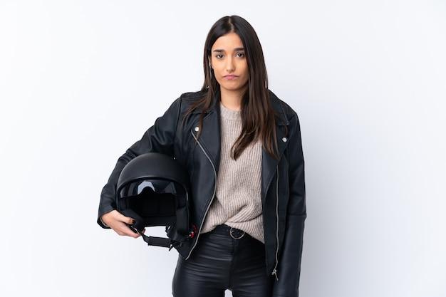 Молодая брюнетка женщина с мотоциклетным шлемом с грустным выражением Premium Фотографии