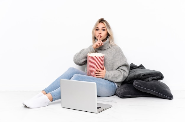 口に指を入れて沈黙ジェスチャーの兆しを見せてラップトップで映画を見ながらポップコーンを食べてティーンエイジャーのブロンドの女の子 Premium写真