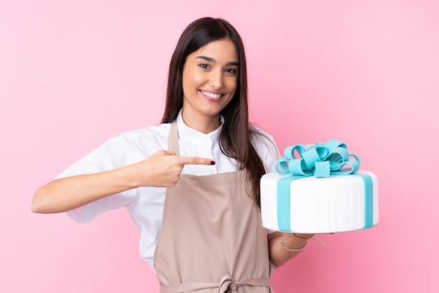 大きなケーキとそれを指している若い女性 Premium写真
