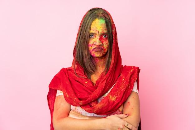 不幸な表情でピンクの壁に彼女の顔にカラフルなホーリーパウダーを持つ若いインド人女性 Premium写真