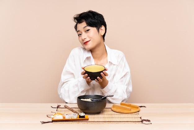 麺と寿司のボウルを持つテーブルで若いアジア女性 Premium写真