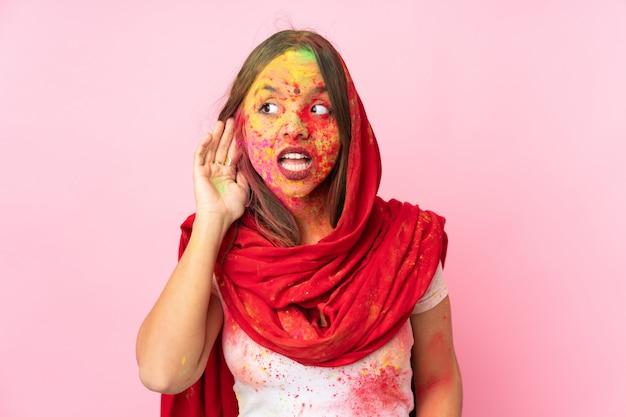 Молодая индийская женщина с красочными порошками холи на лице на розовой стене, слушая что-то, положив руку на ухо Premium Фотографии