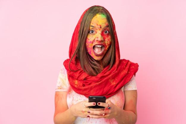 ピンクの壁に彼女の顔にカラフルなホーリーパウダーを持つ若いインド人女性は驚いて、メッセージを送信します Premium写真