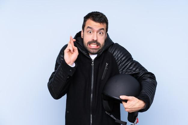 Человек с мотоциклетным шлемом, скрестив пальцы и желая лучшего Premium Фотографии