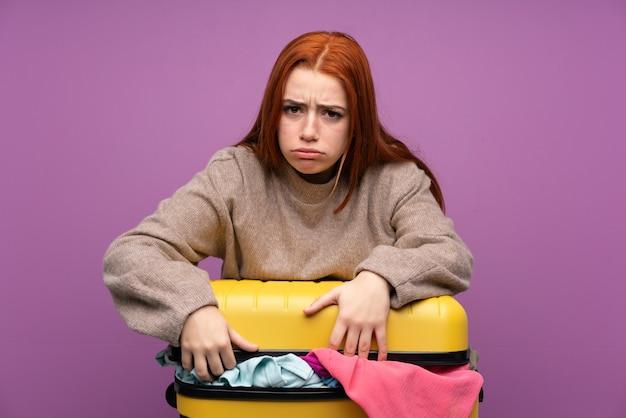 服でいっぱいのスーツケースを持つ旅行者女性 Premium写真