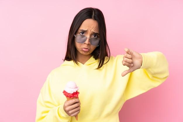 Молодая брюнетка женщина, держащая корнет мороженое, показывая большой палец вниз Premium Фотографии