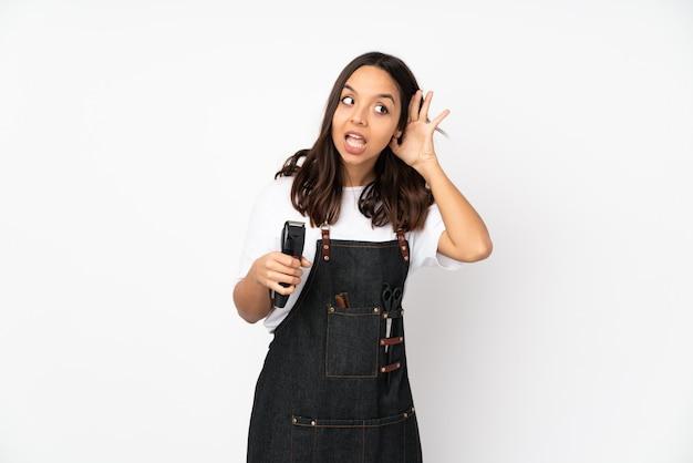 Молодая женщина парикмахер на белой стене, слушая что-то, положив руку на ухо Premium Фотографии