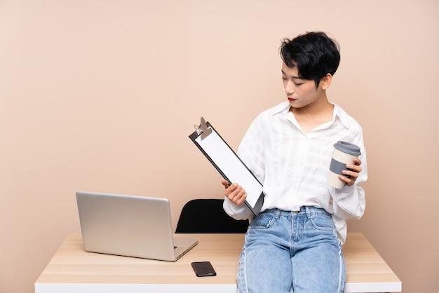 彼女の職場で若いビジネスアジアの女性 Premium写真