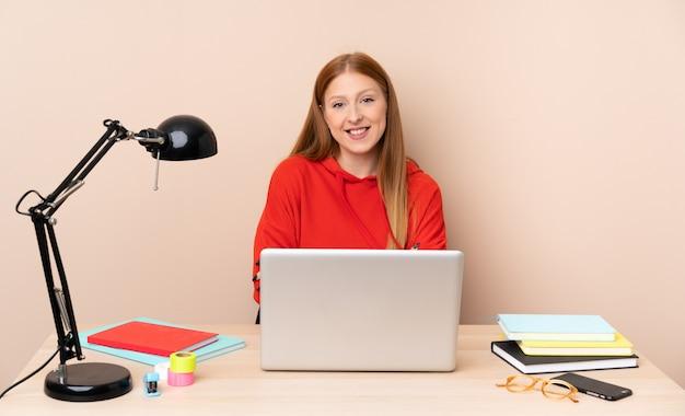 腕を維持するラップトップで職場の若い学生女性が正面の位置で交差 Premium写真