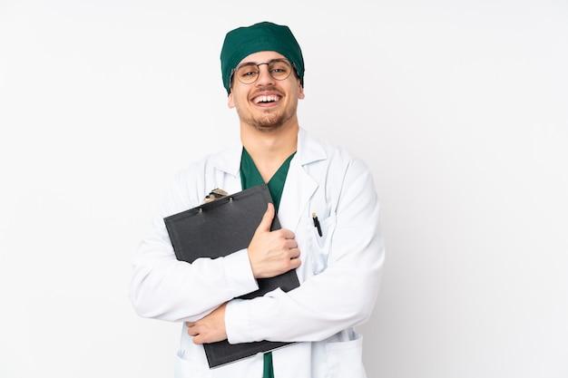孤立した白い壁に緑の制服を着た外科医 Premium写真