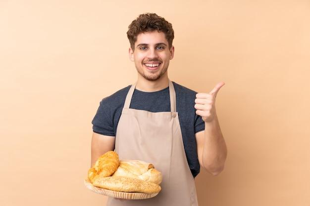 Мужской пекарь держит стол с несколькими хлебов на бежевой стене, давая недурно жест Premium Фотографии