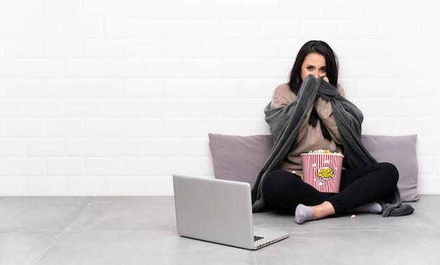 ポップコーンのボウルを保持し、凍結ラップトップで映画を見せて若い女の子 Premium写真