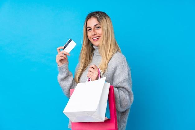 買い物袋とクレジットカードを保持している若いウルグアイ女性 Premium写真