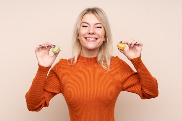 カラフルなフランスのマカロンを保持している若いブロンドのロシア人女性 Premium写真