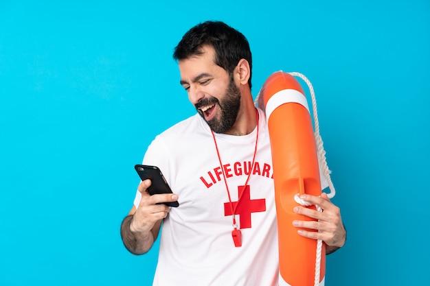Спасатель человек над синей стеной с телефоном в победной позиции Premium Фотографии