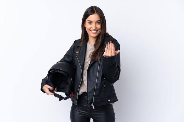 手で来ることを招待して孤立した白い壁にオートバイのヘルメットを持つ若いブルネットの女性。あなたが来て幸せ Premium写真